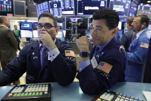 Specialists Robert Tuccillo, left, and Peter Mazza work on the floor of the New York Stock Exchange, Wednesday, July 18, 2018. Stocks are off to a mixed start as gains by industrial and financial companies are offset by energy and technology companies. (AP Photo/Richard Drew)