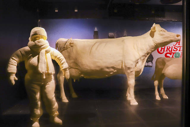 "This Monday, July 16, 2018, photo provided by the American Dairy Association Mideast shows Ohio State Fair butter sculptures including this year's sculptures marking the 35th anniversary of the 1983 movie ""A Christmas Story,"" including the character Randy who ""can't put my arms down"" due to his bulky snowsuit, left, and the display's customary cow and calf, right, in the Dairy Products Building at The Ohio Expo Center & State Fair in Columbus, Ohio. The American Dairy Association Mideast says sculptors spent more than 400 hours creating the refrigerated display unveiled Tuesday, July 24, 2018, crafted from more than a ton of butter. (American Dairy Association Mideast via AP)"