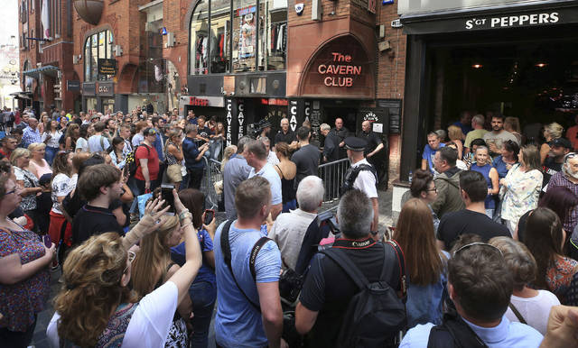 People queue outside the Cavern Club in Liverpool, England, before an exclusive gig by former Beatles member Paul McCartney, Thursday July 26, 2018. The former Beatle will take to the stage at the famous venue on Mathew Street for a one-off exclusive gig. (Peter Byrne/PA via AP)