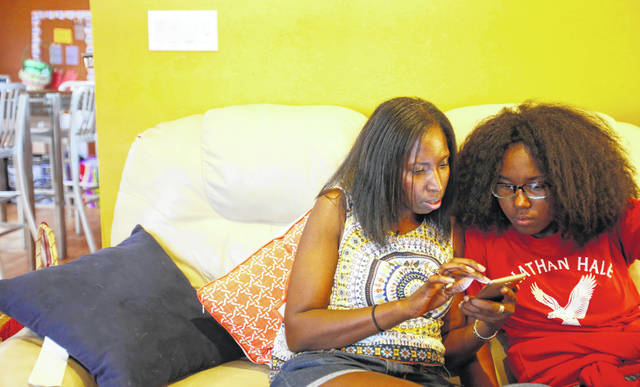 "Jennea Bivens, left, talks with her 13-year-old daughter, Ayrial Miller, about the contacts in her Snapchat social media account while sitting on the couch in their Chicago apartment June 18. Bivens uses a monitoring app to track and limit her daughter's phone use, but she says there's no replacement for a face-to-face conversation, especially about social media. Tracking her daughter's social media, she says, can be ""a full-time job."""