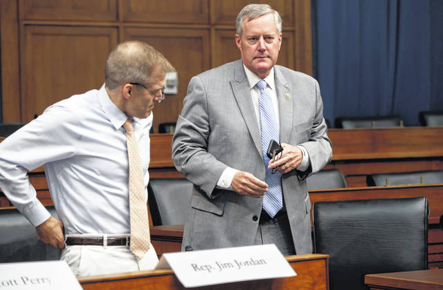 Rep. Mark Meadows, R-N.C., right, chairman of the conservative House Freedom Caucus, and Rep. Jim Jordan, R-Ohio, its founding member, take questions at a news conference on Capitol Hill in Washington on Tuesday. In a Monday letter to the Department of Justice inspector general, Meadows and Jordan asked for a review of allegations that Deputy Attorney General Rod Rosenstein threatened to subpoena phone records and documents from a House Intelligence Committee staffer.
