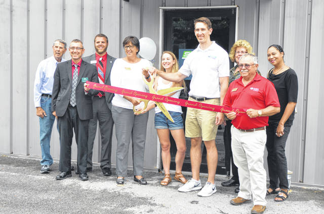 Bill Lamont, Dave Compton, Jason May, Cindy Tenwalde, Grace Meuleman, Dr. Cory Meuleman, Sheila Custer, Wally Kincaid and Heather Jordan help cut the ribbon at the Surge Chiropractic grand opening at 3477 South Dixie Highway, Suite A, Friday.