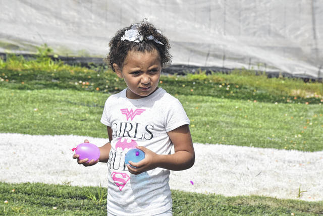 K.J. Hood, 4, of Lima, contemplates her next target in a water balloon war at Crosshairs Lima.