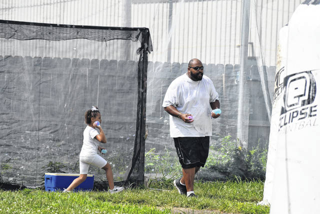 K.J. Hood, 4, sneaks up on her dad James at a water balloon war at Crosshairs Lima.