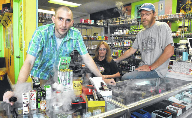 DG Essentials staff display some of the new CBD vapes. Pictured: Chad Reeder, left, director of operations, Denise Guagenti, owner, and Kirk Sneed, manager.