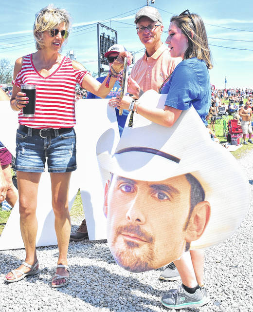 Left to right, Lori Alters, of Osgood, and Dave Wolters, of Maria Stein, talk to Katie Hausfeld, of Vandalia, who was promoting Brad Paisley with a giant cut-out of Paisley's head.