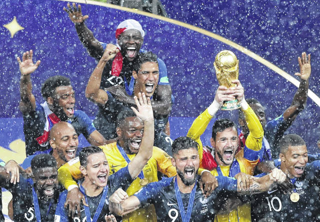 France players celebrate with the trophy after defeating Croatia in the final at the 2018 soccer World Cup in the Luzhniki Stadium in Moscow, Russia, Sunday, July 15, 2018. (AP Photo/Rebecca Blackwell)
