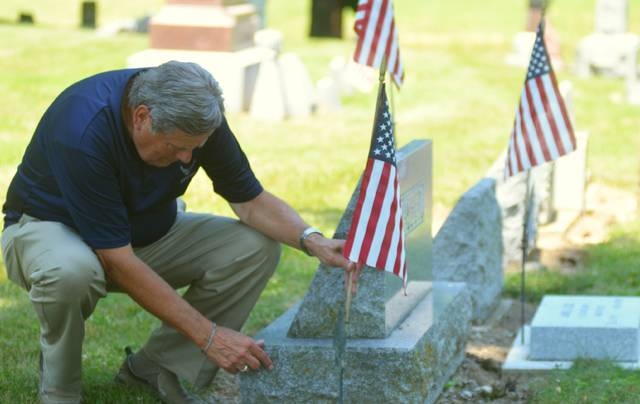 Bill Marshall tends to the American flags marking the graves of veterans in Woodland Cemetery near James Coe's final resting place.