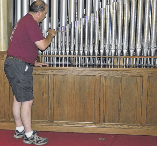 Tom Densel, Lima Pipe Organ Co. employee of over 33 years, uses a tuning instrument to evaluate the sound of the pipe organ at St. Luke Lutheran Church, Lima.