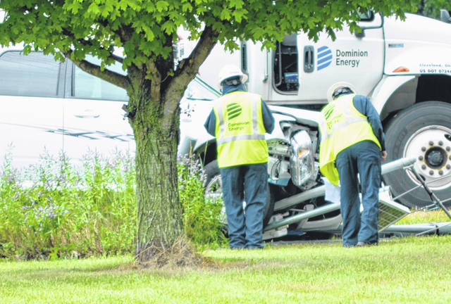 Dominion Energy workers hurry to install a valve so a gas leak could be stopped Friday afternoon after a crash on state Route 117 near Copus Road. Traffic was routed around the area for hours.
