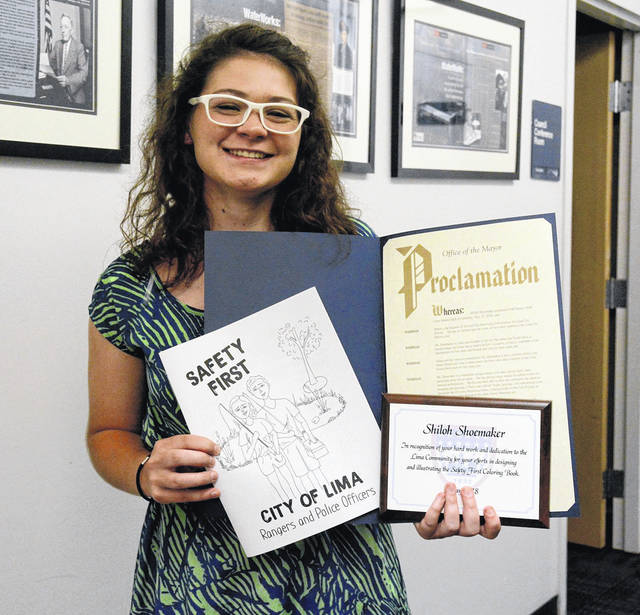"Lima Senior graduate Shiloh Shoemaker shows off the ""Safety First"" coloring book she helped design and a proclamation she was awarded recently by Lima Mayor David Berger."