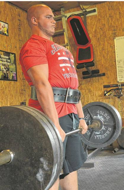 Gage Hovest, 17, of Pandora, current strongman middle weight teen national champion and national record holder for pressing a 200 pound Mouser Block, performs a dead lift..