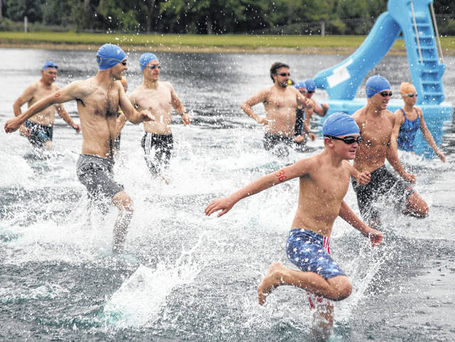 Connor Raines (right front), 11, leads the charge into the coool waters at Ottawa Metro Park to begin the Lima YMCA/Kewpee Triathlon/Duathlon Sunday.