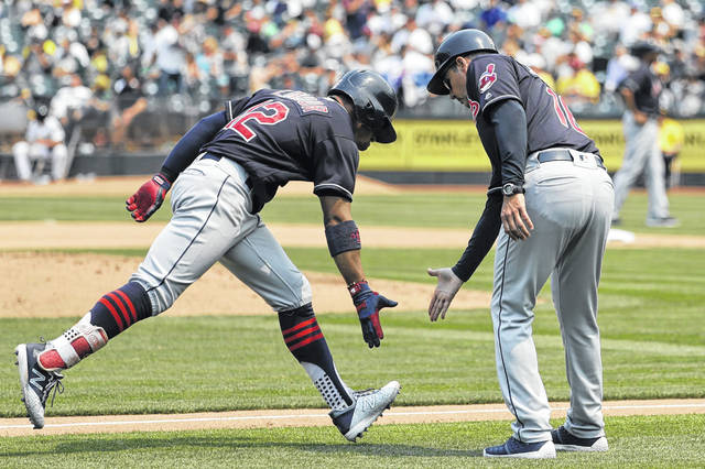 Cleveland Indians' Francisco Lindor accepts the congratulation of third base coach Mike Sarbaugh after hitting a solo home run against the Oakland Athletics during the seventh inning of the Indians' 15-3 win on Sunday.
