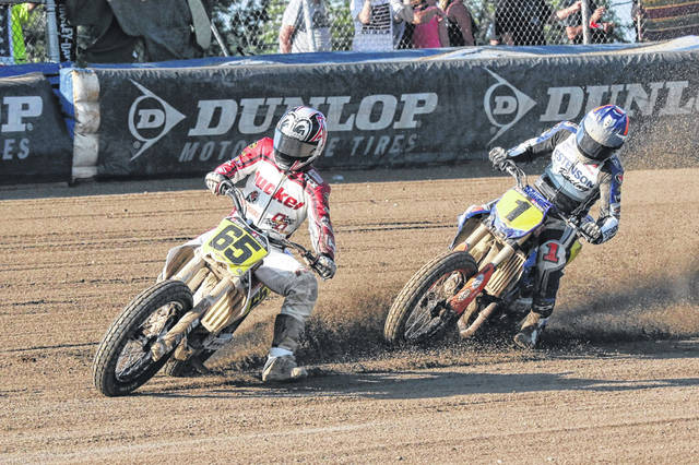 Cory Texter (65) and Kolby Carlile (1) lean into a turn during the Singles competition at the American Flat Track motorcycle races Saturday night at the Allen County Fairgrounds.