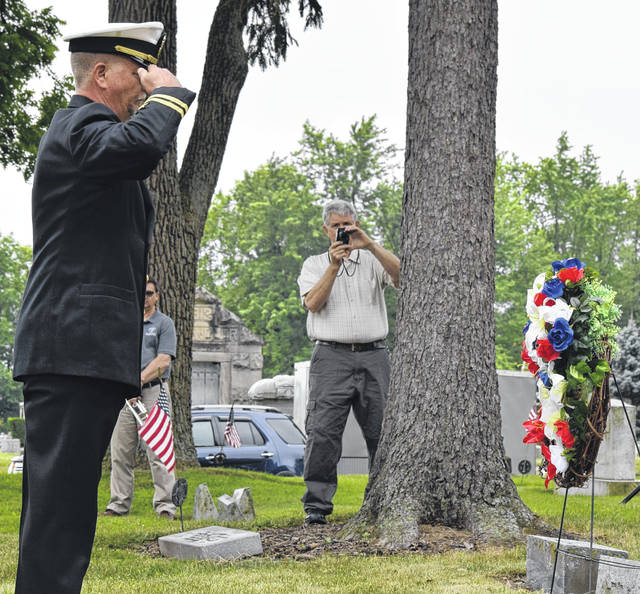 Lt. Pete Weir places a wreath on the previously unmarked grave of James L. Coe in ceremonies Saturday at Woodland Cemetery in Van Wert. Jim Wilson, a direct descendant of Coe snaps a picture of the moment.
