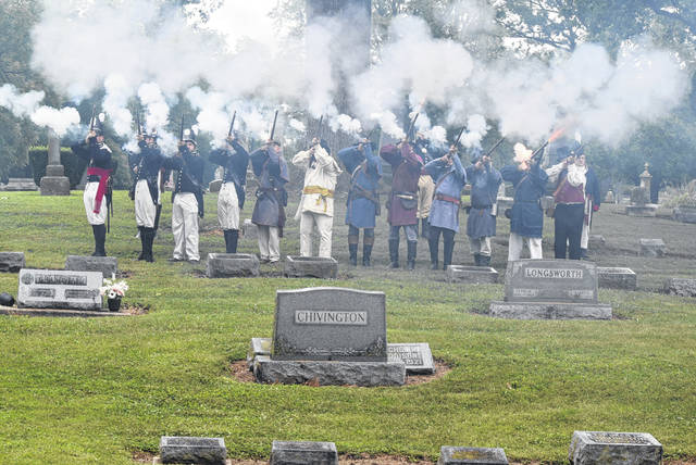 Re-enactors fire a 21-Gun Salute at a ceremony remembering James L. Coe, who had an unmarked grave, until recently at Woodland Cemetery in Van Wert.