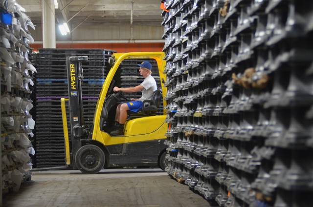 Warehouse worker Drew Jacobs drives a forklift through the stacked tire rims stored within the old K-Mart building in St. Marys.
