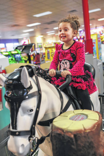 Autumn Jones, of Lima, rides on a mechanical horse at Chuck E. Cheese's.