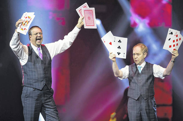 "FILE - In this Dec. 1, 2017, file photo, Penn Jillette, left, and Raymond Teller perform their ""Penn & Teller"" act at the Vegas Strong Benefit concert in Las Vegas. The duo cancelled a performance scheduled for Friday, July 6, in Biloxi, Miss., because Teller's back injury has flared up."