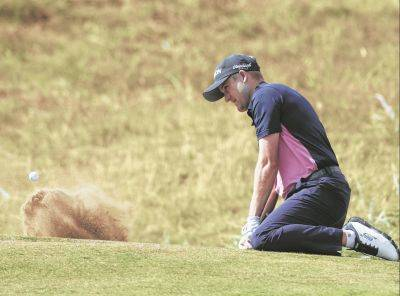 Russell Knox plays out of a bunker on the first hole during Thursday's first round of the British Open in Carnoustie, Scotland.