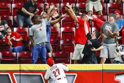 Cincinnati Reds right fielder Phillip Ervin (27) watches as fans reach for a two-run home run hit by the St. Louis Cardinals' Dexter Fowler off Amir Garrett during the 11th inning of Tuesday night's game in Cincinnati. The Cardinals won 4-2. (AP photo)