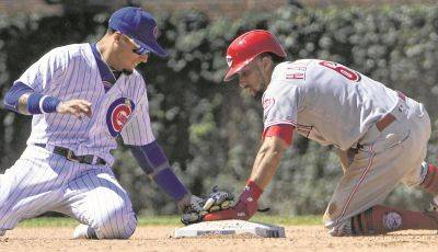 Cincinnati's Billy Hamilton touches second base to record a stolen base before the Cubs' Javier Baez can make the tag during Saturday's game in Chicago.