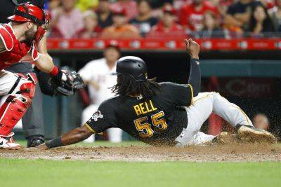 Pittsburgh's Josh Bell (55) is tagged out at home by the Reds' Curt Casali in the eighth inning Saturday night's game in Cincinnati. (AP photo)