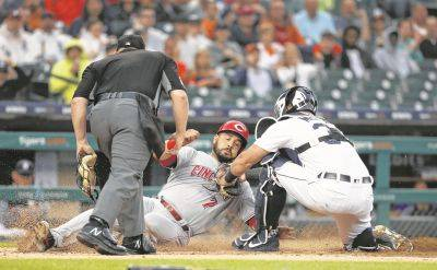 Umpire Sean Barber watches as the Tigers' James McCann tags out Cincinnati's Eugenio Suarez at home plate during the second inning of Tuesday night's game in Detroit.