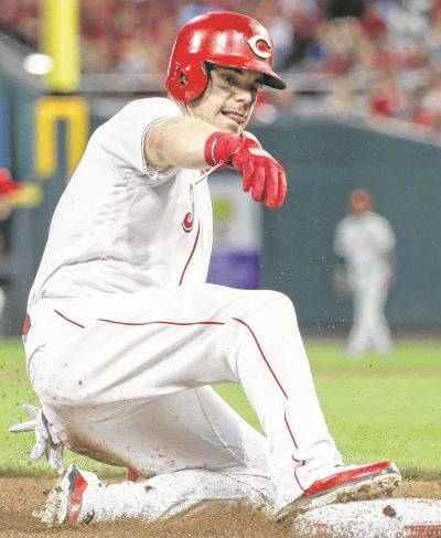 Cincinnati Reds' Scooter Gennett slides into third on an RBI single by Joey Votto off Philadelphia Phillies relief pitcher Tommy Hunter in the sixth inning of a baseball game, Saturday, July 28, 2018, in Cincinnati. (AP Photo/John Minchillo)