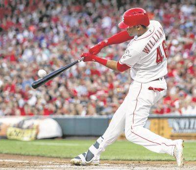 The Reds' Mason Williams hits a three-run home run during Friday night's game against Philadelphia in Cincinnati.