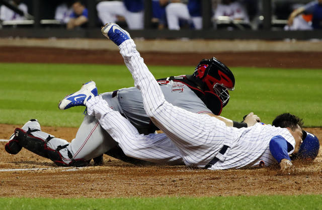 Cincinnati Reds catcher Tucker Barnhart (16) tags out New York Mets' Wilmer Flores (4) at home plate during the third inning of a baseball game Monday, Aug. 6, 2018, in New York. (AP Photo/Frank Franklin II)