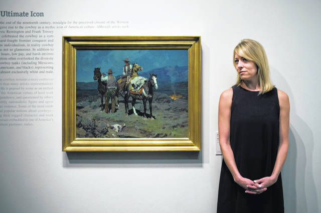 "Chief curator Amy Scott pauses for photos with a painting titled ""First Streak of Dawn"" by Frank Tenney Johnson at the Autry Museum of the American West, in Los Angeles in 2007. A federal judge in Nevada has thrown out a defamation suit this month that a Western art collector, Gerald Peters of New Mexico, filed against a prestigious auction house and the owner of a Reno gallery because they claimed a different 1937 cowboy painting Peters sold for $750,000 — ""The Sun and the Rain"" — was not one of Johnson's original works."