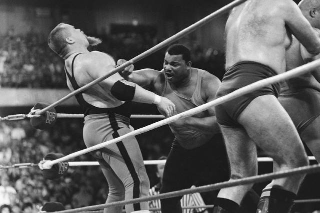 """File - This April 7, 1986, file photo shows Chicago Bears' William Perry, right, landing a punch on pro wrestler Jim """"The Anvil"""" Neidhart during the """"Over-The-Top-Rope"""" battle royal at Wrestlemania 2 in Rosemont, Ill. Neidhart, who joined with Bret Hart to form one of the top tag teams in the 1980s with the WWE, has died. He was 63. The Pasco Sheriff's Office said Neidhart fell at home, hit his head and """"succumbed to his injury"""" on Monday, Aug. 13, 2018, in Wesley Chapel, Fla. No foul play was suspected."""