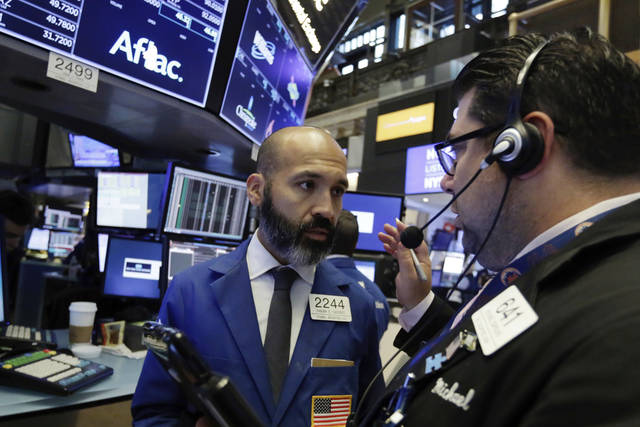 Specialist Fabian Caceres, left, and trader Michael Capolino confer on the floor of the New York Stock Exchange, Tuesday, Aug. 14, 2018. Stocks are broadly higher and recovering some of their recent losses as concerns about Turkey's financial stability eased. (AP Photo/Richard Drew)