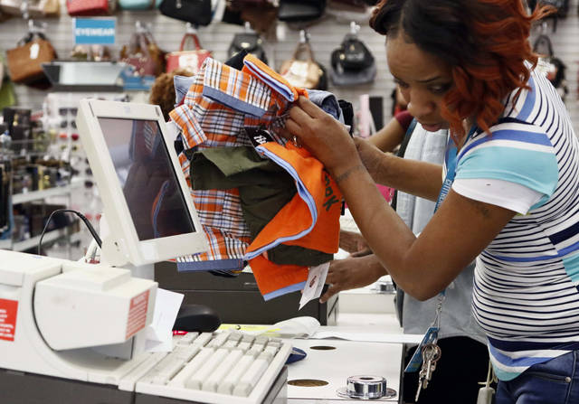 FILE- In this July 27, 2018, file photo, Crystal Bowman, manager of Citi Trends clothing store, counts the school clothes and school uniforms of a customer in Jackson, Miss. On Wednesday, Aug 15, the Commerce Department releases U.S. retail sales data for July. (AP Photo/Rogelio V. Solis, File)