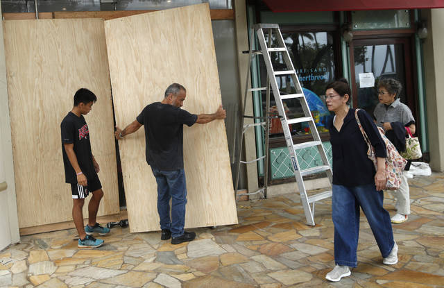 James Fujita, left, and Reid Fujita take down plywood boards that were to protect their store from Tropical Storm Lane along Waikiki Beach, Saturday in Honolulu. Federal officials said Saturday that torrential rains are now the biggest threat to Hawaii after the once-powerful hurricane that threatened the island state was downgraded to a tropical storm, and they urged people to continue to take the storm seriously.