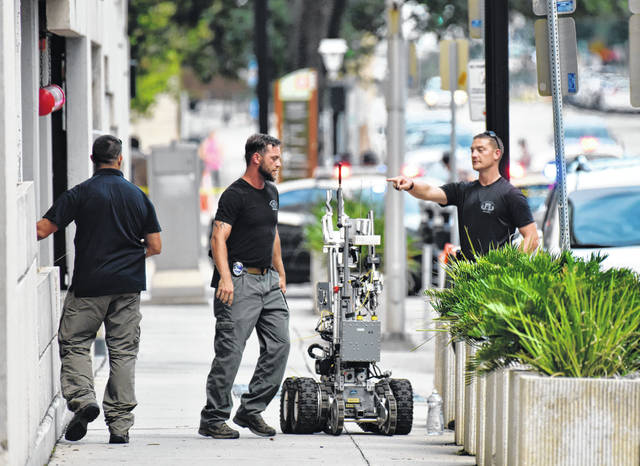 Bomb squad police prepare a robot to enter a parking garage a block away from the scene of a multiple shooting at the Jacksonville Landing Sunday during a video game competition in Jacksonville, Fla. A gunman opened fire Sunday during an online video game tournament that was being livestreamed from a Florida mall, killing multiple people and sending many others to hospitals, authorities said.