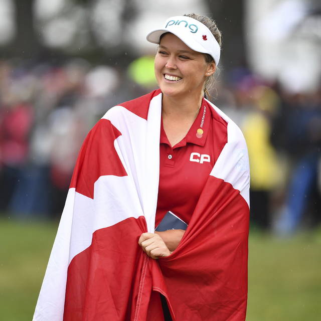 Canada's Brooke Henderson is wrapped in a Canadian flag as she celebrates her win at the Women's Canadian Open golf tournament in Regina, Saskatchewan, Sunday Aug. 26, 2018. (Jonathan Hayward/The Canadian Press via AP)