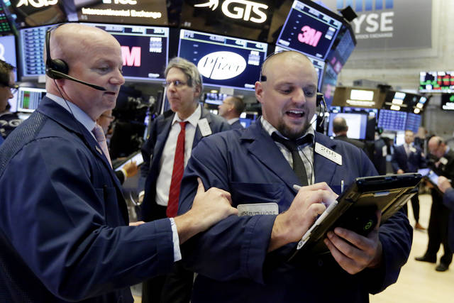 Traders Patrick Casey, left, and Michael Milano work on the floor of the New York Stock Exchange, Tuesday, Aug. 28, 2018. Stocks are opening broadly higher on Wall Street as stocks add to the records they've set in the last few days. (AP Photo/Richard Drew)