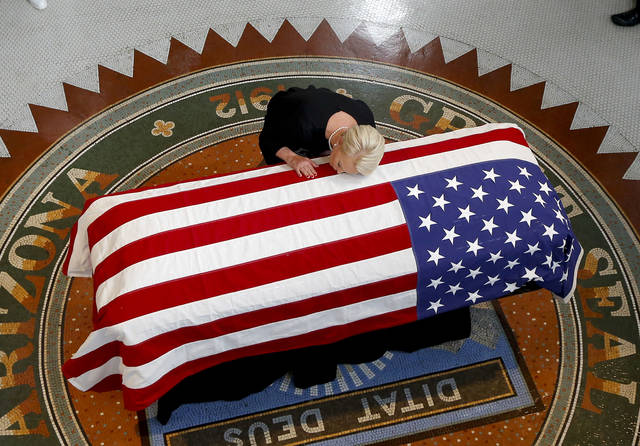 Cindy McCain, wife of, Sen. John McCain, R-Ariz. lays her head on casket during a memorial service at the Arizona Capitol on Wednesday, Aug. 29, 2018, in Phoenix. (AP Photo/Ross D. Franklin, Pool)