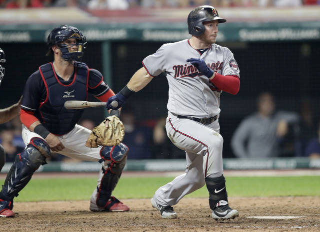 Minnesota Twins' Robbie Grossman watches his two-run single off Cleveland Indians relief pitcher Cody Allen during the seventh inning of a baseball game, Wednesday, Aug. 29, 2018, in Cleveland. At left is Indians catcher Yan Gomes. (AP Photo/Tony Dejak)