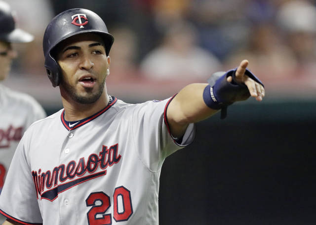 Minnesota Twins' Eddie Rosario points to Robbie Grossman after Grossman hit a two-run single in the seventh inning of a baseball game against the Cleveland Indians, Wednesday, Aug. 29, 2018, in Cleveland. Rosario scored on the play. (AP Photo/Tony Dejak)