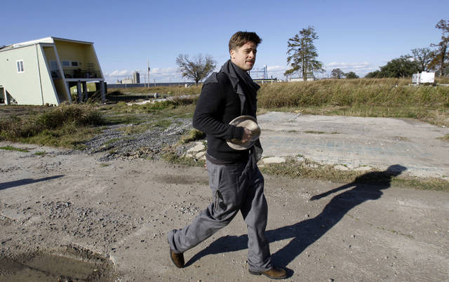 In this Dec. 1, 2008, file photo, Brad Pitt walks in the Lower 9th Ward between a home built by the Make It Right Foundation and a FEMA trailer in New Orleans. An attorney plans to sue Pitt's foundation over the degradation of homes built in an area of New Orleans that was among the hardest hit by Hurricane Katrina.