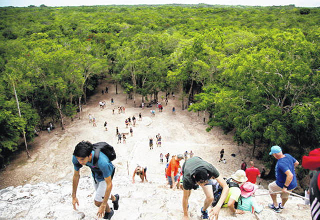 Tourists climb a temple at the archeological site of Coba, in Mexico's Yucatan Peninsula, earlier this month. Whether you're planning a trip to a country across the globe or packing the car for a weekend road trip to a local campground, you can have a debt-free vacation with some careful planning.