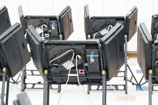 FILE - This Tuesday, Aug. 7, 2018 file photo shows electronic voting machines in a polling station in Dublin, Ohio. With Ohio's special election for the 12th Congressional District still too close to call, questions have been raised about the veracity of voter rolls in the swing state.