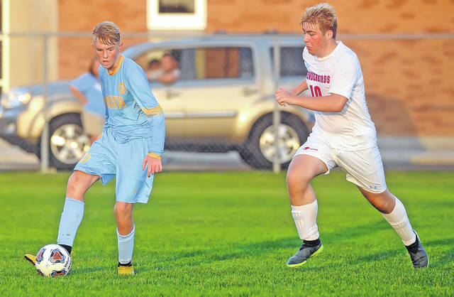 Lima Central Catholic's Billy Blankmeyer defends Bath's Jonathan Wiggins during a Bath Kickoff Classic semifinal Tuesday night at Bath High School.
