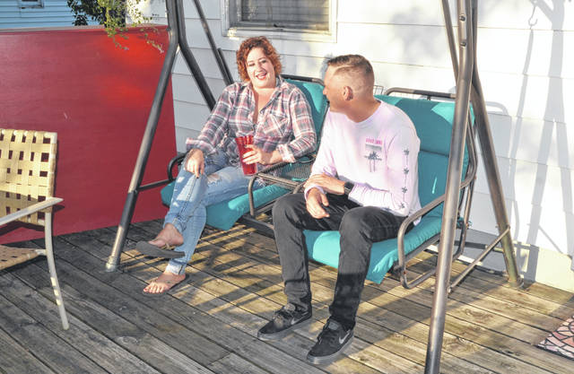 Lima Airbnb host Ambyr Rose and new Pro-Tec Coating Company employer Brad Stigall converse on her deck outside her home in Lima. Stigall is Rose's Airbnb guest who recently relocated from Fairfield to Lima for a one-year temporary position at Pro-Tec Coating Company.