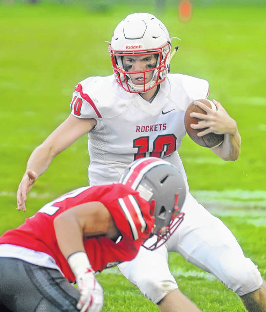 Pandora-Gilboa's Jared Breece scrambles for yards against Columbus Grove's Caleb Barrientes during Friday night's game at Clymer Stadium in Columbus Grove.