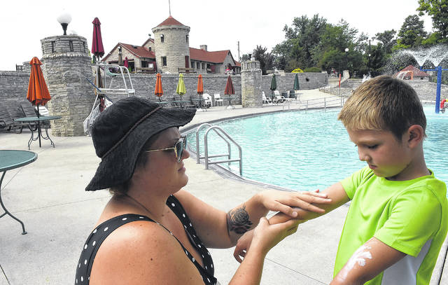 Stacey Amstutz of Findlay, rubs sunscreen on her son, Sawyer, 6, before swimming at Columbus Grove Municipal Pool.